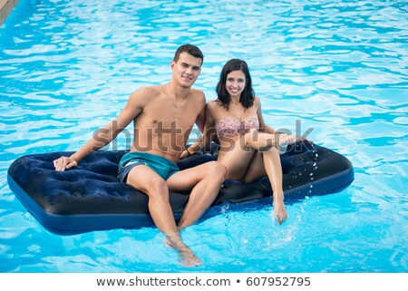 young man and nice women lying on an inflatable mattress in pool stock photo © Paha_L