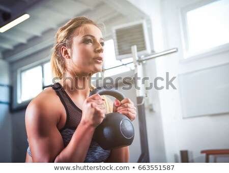 young woman lifting a kettlebell stock photo © sumners
