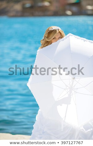 beautiful bride in wedding dress hidden by white umbrella posing stock photo © victoria_andreas