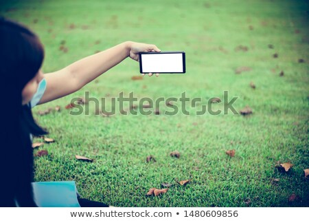 Retro toned adult female hands using mobile phone outdoors Stock photo © stevanovicigor