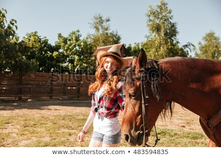 smiling cowgirl holding and walking with her horse on ranch stock photo © deandrobot
