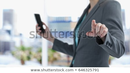 Midsection of businesswoman holding smart phone while pointing in city 商業照片 © wavebreak_media