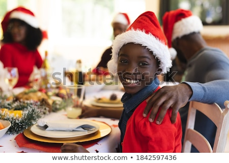 Young girl wearing party hat at table smiling Stock photo © monkey_business