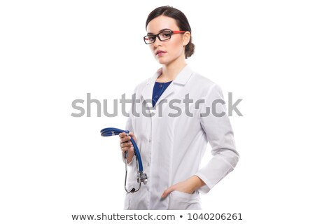 young woman doctor holding stethoscope in one hand and her other hand in pocket in white uniform on stock photo © traimak