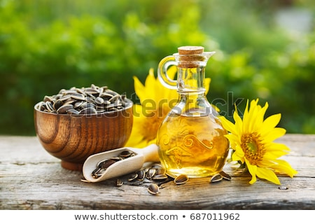 Sunflower oil in glass jar, seeds and flowers stock photo © Illia