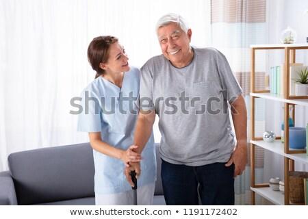 Caretaker Assisting Senior Man While Walking At Home Stock photo © AndreyPopov