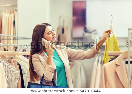 woman calling on smartphone at clothing store stock photo © dolgachov