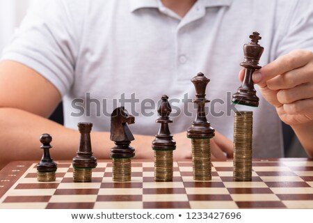 man placing king chess piece over stacked coins stock photo © andreypopov