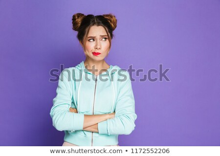 Portrait of confused woman with two buns twisting mouth and look Stock photo © deandrobot