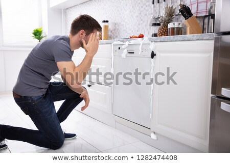 Upset Man Sitting In Front Of Damaged Dishwasher Stock photo © AndreyPopov