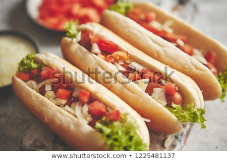 Three barbecue grilled hot dogs with sausage placed on wooden cutting board Stock photo © dash