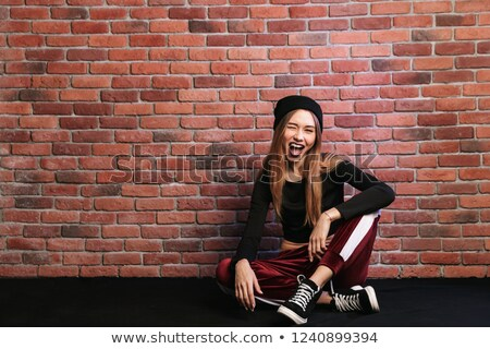 Photo of beautiful young hip hop dancer or sporty girl, sitting  Stock photo © deandrobot
