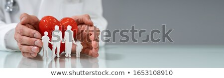 close up of family cut out red heart shape and stethoscope stock photo © andreypopov