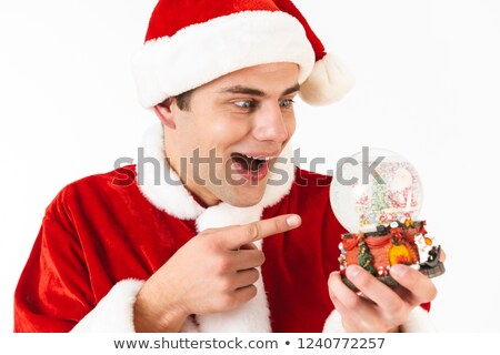 Image of joyous man 30s in santa claus costume and red hat holdi Stock photo © deandrobot