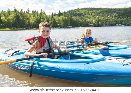 Summer vacation Portrait of happy cute boy kayaking the on river Stock photo © Lopolo