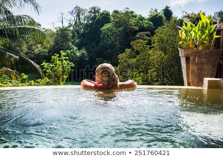 Woman in tropical vacation enjoying the jungle from the pool Stock photo © Kzenon