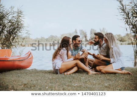 Group of friends with cider bottles sitting by the boat near the Stock photo © boggy