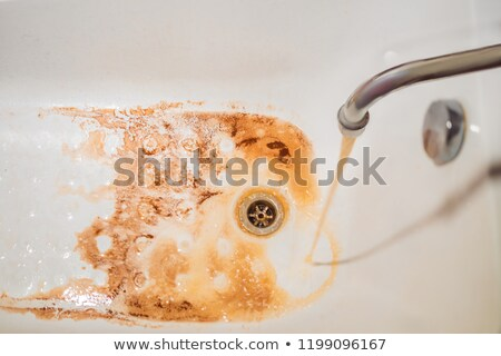 Dirty brown running water falling into a white sink from tap. Environmental pollution concept Stock photo © galitskaya