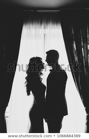 Stok fotoğraf: Portrait Of A Romantic Couple Silhouette Couple Of Lovers Groom And Bride At The Window