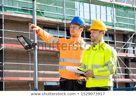Supervisor Looking At Architect Writing On Clipboard Stock photo © AndreyPopov
