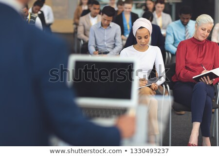 Front view of diverse group of business people writing notes at a business seminar in modern office  Stock photo © wavebreak_media