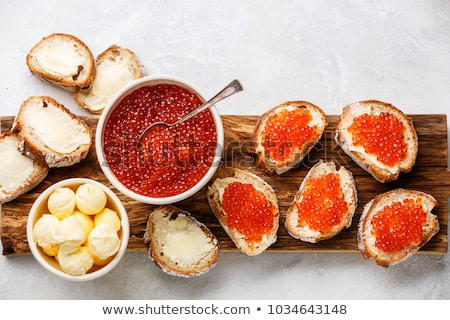 Salmon red caviar in bowl and Sandwiches with on wooden cutting board Stock photo © Illia