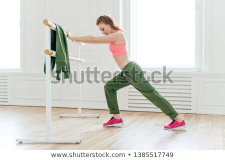Sport, recreation, flexibility concept. Motivated strong female makes plank, leans at ballet barre,  Stock photo © vkstudio