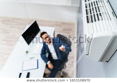 Businessman Using Remote Control In Front Of Air Conditioner Stock photo © AndreyPopov
