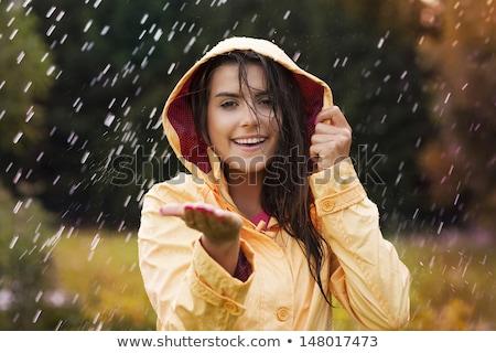 Beautiful young woman in raincoat checking for rain Stock photo © elenaphoto