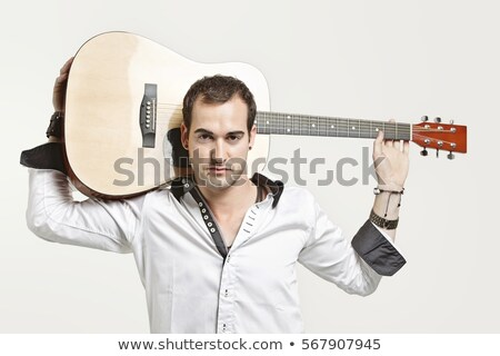 Serious young man with his guitar over his shoulder Stock photo © photography33