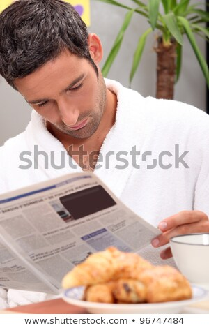 Handsome man in a toweling robe reading a journal Stock photo © photography33
