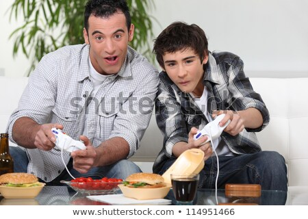 Stock photo: Father and son playing video games and eating junk-food