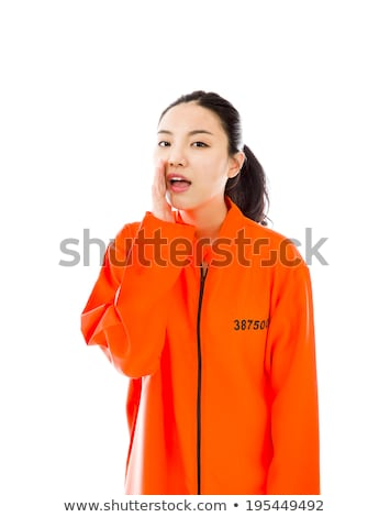 young asian woman whispering in prisoners uniform stock photo © bmonteny