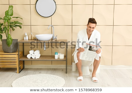 Stock photo: Man In Toilet Reading Newspaper