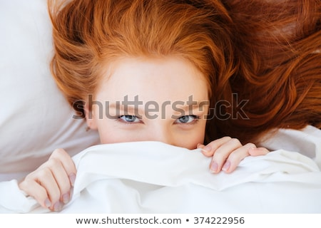 cute lovely woman with red hair hiding under white blanket stock photo © deandrobot