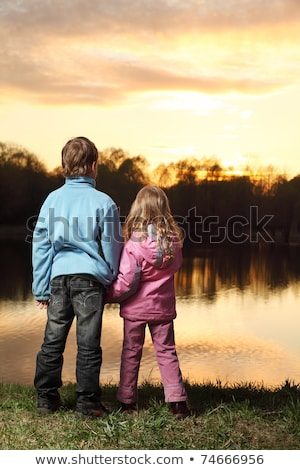 Girl on boys back standing in  water stock photo © stockfrank