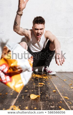 Man throwing potato chips from packet into the camera Stock photo © deandrobot