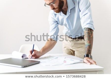 Cropped photo of young readhead bearded man working with papers Stock photo © deandrobot