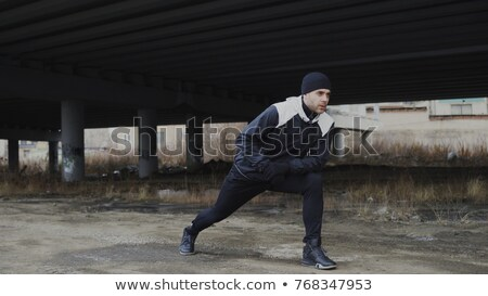 Male runner training in cold winter doing warm-up leg stretching Stock photo © snowing