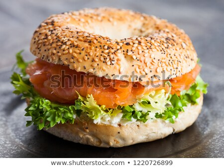 fresh healthy bagel sandwich with salmon ricotta and lettuce on black plate on black kitchen table stock photo © denismart