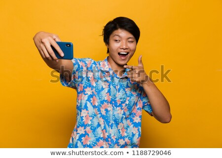 happy young asian man standing isolated over yellow background take a selfie by mobile phone stock photo © deandrobot