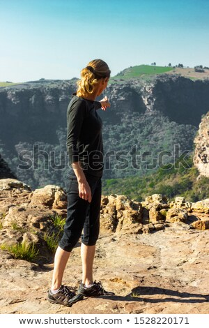 hiker standing on the mountain ledge looking out to the valley beyond stock photo © lovleah