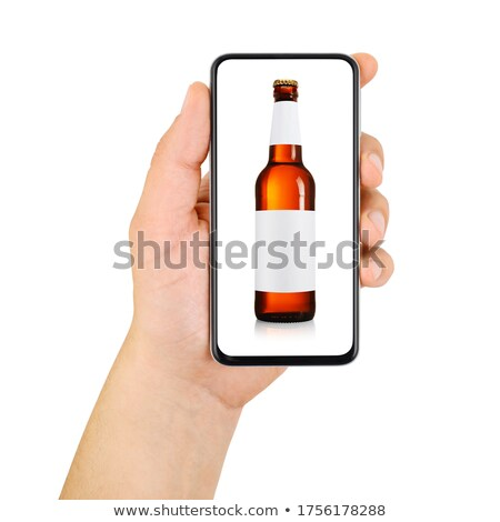 close up of man with smartphone and alcohol bottle stock photo © dolgachov