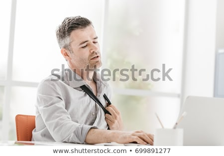 Nervous businessman working in a very hot office, he is sweating and loosening his tie Stock photo © Minervastock