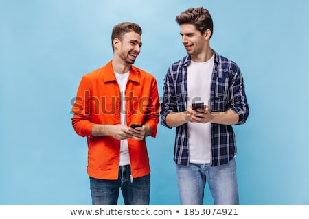 Excited young man wearing plaid shirt Stock photo © deandrobot