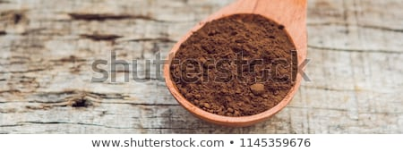 Carob powder in a wooden spoon on an old wooden background BANNER, long format Stock photo © galitskaya