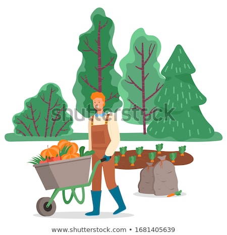 smiling man working on field cart with pumpkin stock photo © robuart