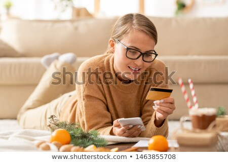 young casual woman with smartphone and credit card looking at personal data stock photo © pressmaster
