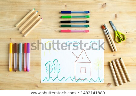 Pencils, pens, scissors and paintbrushes surrounding kid drawing of house Stock photo © pressmaster