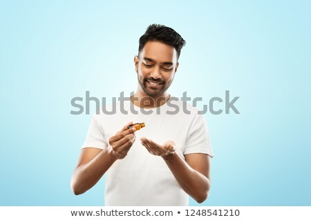 indian man applying grooming oil to his hand Stock photo © dolgachov